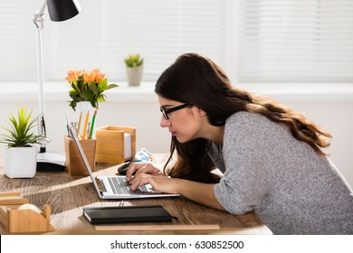 Businesswoman Sitting In Wrong Posture Working On Laptop On Wooden Office Desk
