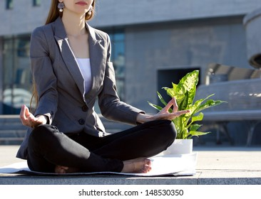 businesswoman sitting in yoga pose, near - flower in pot, on blurred building  background