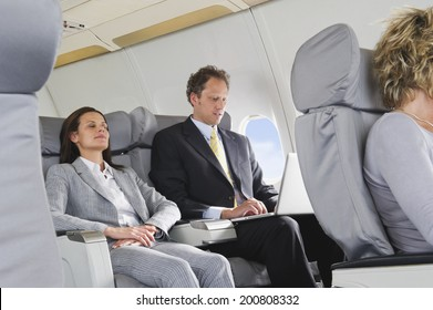 Businesswoman sleeping and businessman working on laptop on airplane