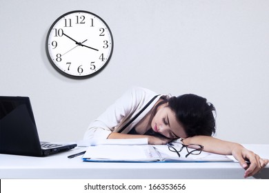 Businesswoman sleeping with laptop computer on the desk in office