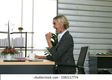 Businesswoman in smart suits glad for the work result on the table. Business successful concept, Happy excited woman at work place