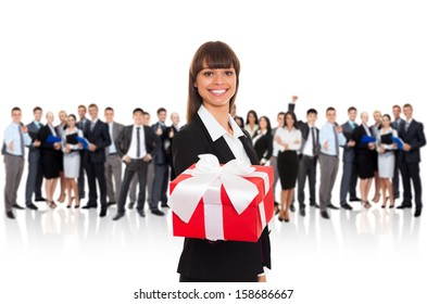 Businesswoman smile present gift red box in hand. Woman over big group of Business people on background