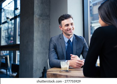 Businesswoman and smiling businessman discussing in restaurant