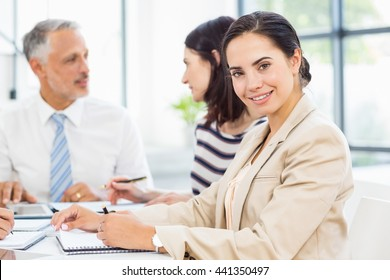 Businesswoman smiling at camera while colleagues discussing in the background