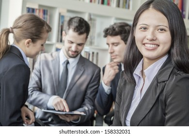 Businesswoman smiling and looking at camera with her colleagues talking in the background