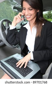 Businesswoman smiling on the phone in the car