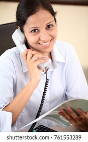 Businesswoman speaking on phone at her office