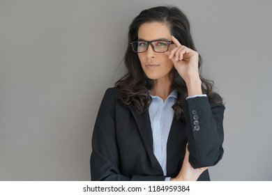 Businesswoman with spectacles standing on grey background