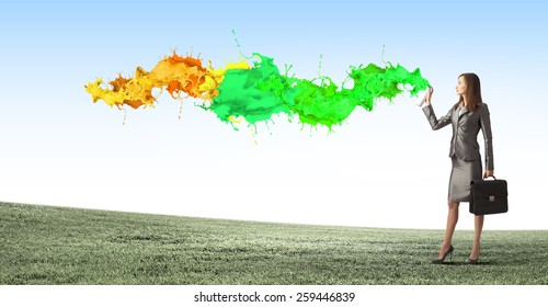 Businesswoman spraying colorful paint splashes from container