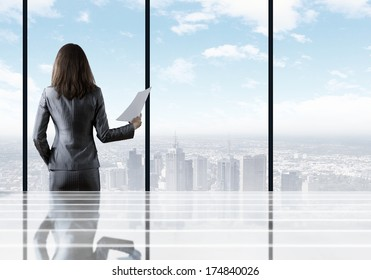 Businesswoman standing with back against office window holding documents in hand