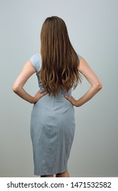 Businesswoman standing back studio portrait of woman with long hair.