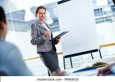 A businesswoman standing by whiteboard and looking at her partners