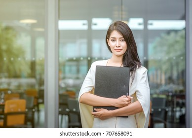 Businesswoman standing holding a document file