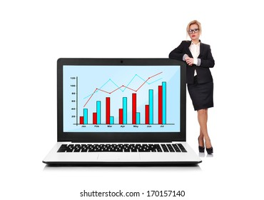 businesswoman standing near a laptop with chart