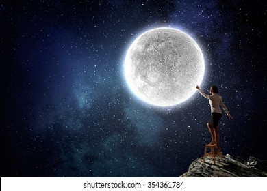 Businesswoman standing on chair and reaching hand to touch moon