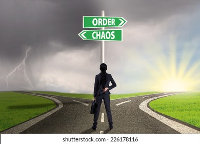 Businesswoman standing on the road looking at signpost of order and chaos