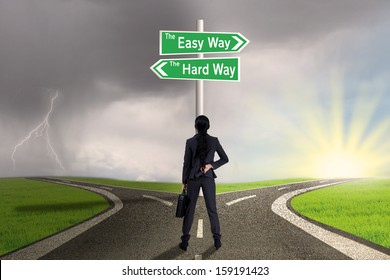 Businesswoman is standing on the road with sign of easy vs hard way