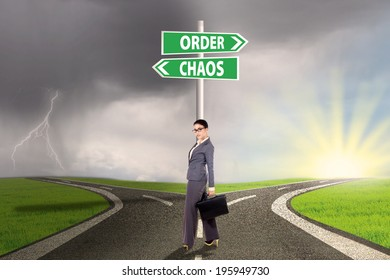 Businesswoman standing on the road with signpost of order and chaos