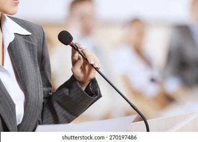 Businesswoman standing on stage and reporting for audience