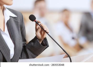 Femme d'affaires debout sur scène et présentant des informations pour le public