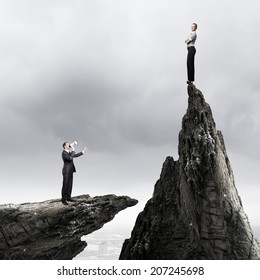 Businesswoman standing on top of rock and businessman screaming in megaphone