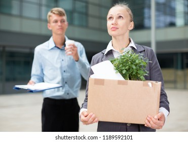 Businesswoman is standing pensive near office because she pending leave.