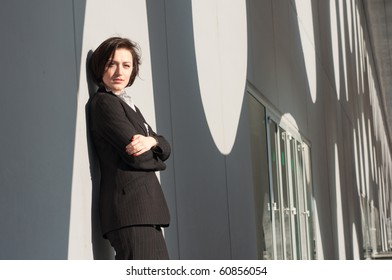 Businesswoman standing and posing at the wall outside