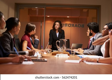 Businesswoman stands addressing team at meeting, low angle