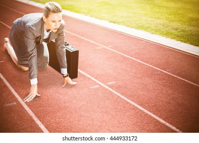 Businesswoman in starting position against focus on track on a sunny day