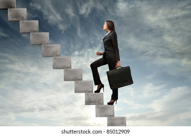 Businesswoman stepping up a stairway with sky in the background
