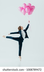 businesswoman in suit and ballet shoes holding pink balloons, isolated on grey