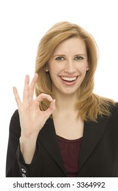"A businesswoman in a suit gestures ""ok"""