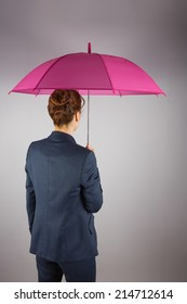 Businesswoman in suit holding pink umbrella on grey background