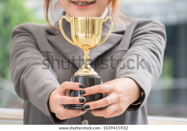 Businesswoman with suit are holding trophy cup with success work.