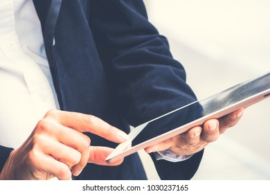 Businesswoman with suit using tablet for communication. Side view of businesswoman checking mail from her customer by tablet with success work.