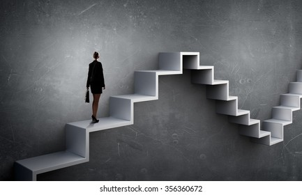 Businesswoman with suitcase stepping up stone staircase