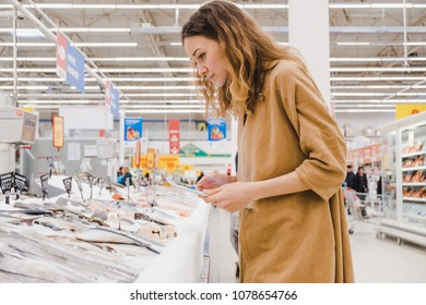 Businesswoman with a tablet picks fish in a supermarket