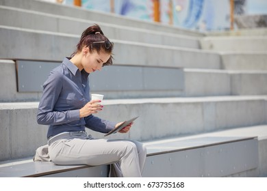 Businesswoman with a tablet  sits on a concrete wall. Online education students
