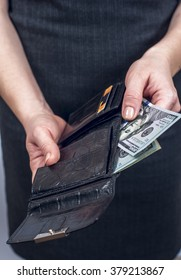 Businesswoman takes out dollars from leather wallet. Conception of safe storage and protection of cash. Financial theme.