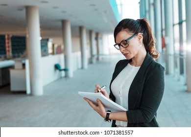 Businesswoman taking note standing in office building.