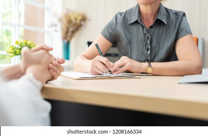 Businesswoman is taking notes on clipboard during the job interview.