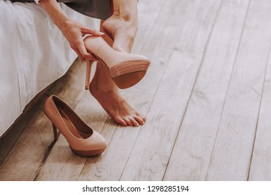 Businesswoman taking off high heels shoes after work at home. Close up of her legs