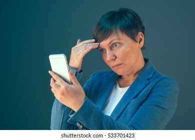 Businesswoman taking selfie portrait with mobile phone before important business meeting in office