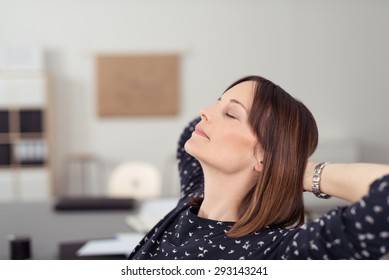 Businesswoman taking time out at work relaxing in her chair at the office with her head tilted back on her clasped hands and eyes closed