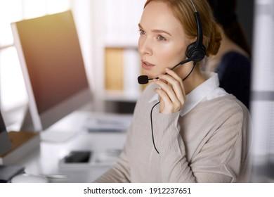 Geschäftsfrau, die im sonnigen Büro mit Headset spricht. Call-Center und verschiedene Personengruppen