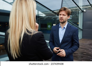 Businesswoman talking with her business partner standing near skyscraper office, confident businesspeople having serious conversation about the work, boss discussing with employee