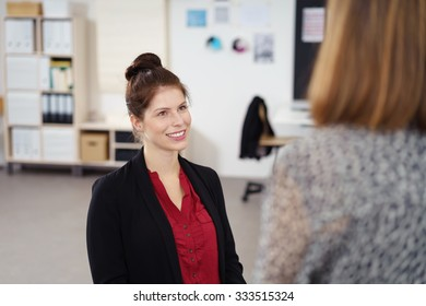 businesswoman talking to her colleague at the office with a friendly facial expression
