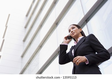 Businesswoman talking on cell phone outside modern office building