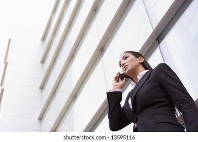 Businesswoman talking on cell phone outside modern office