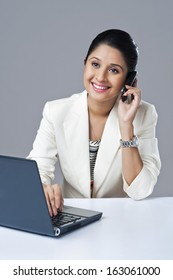 Businesswoman talking on a mobile phone while using a laptop in an office
